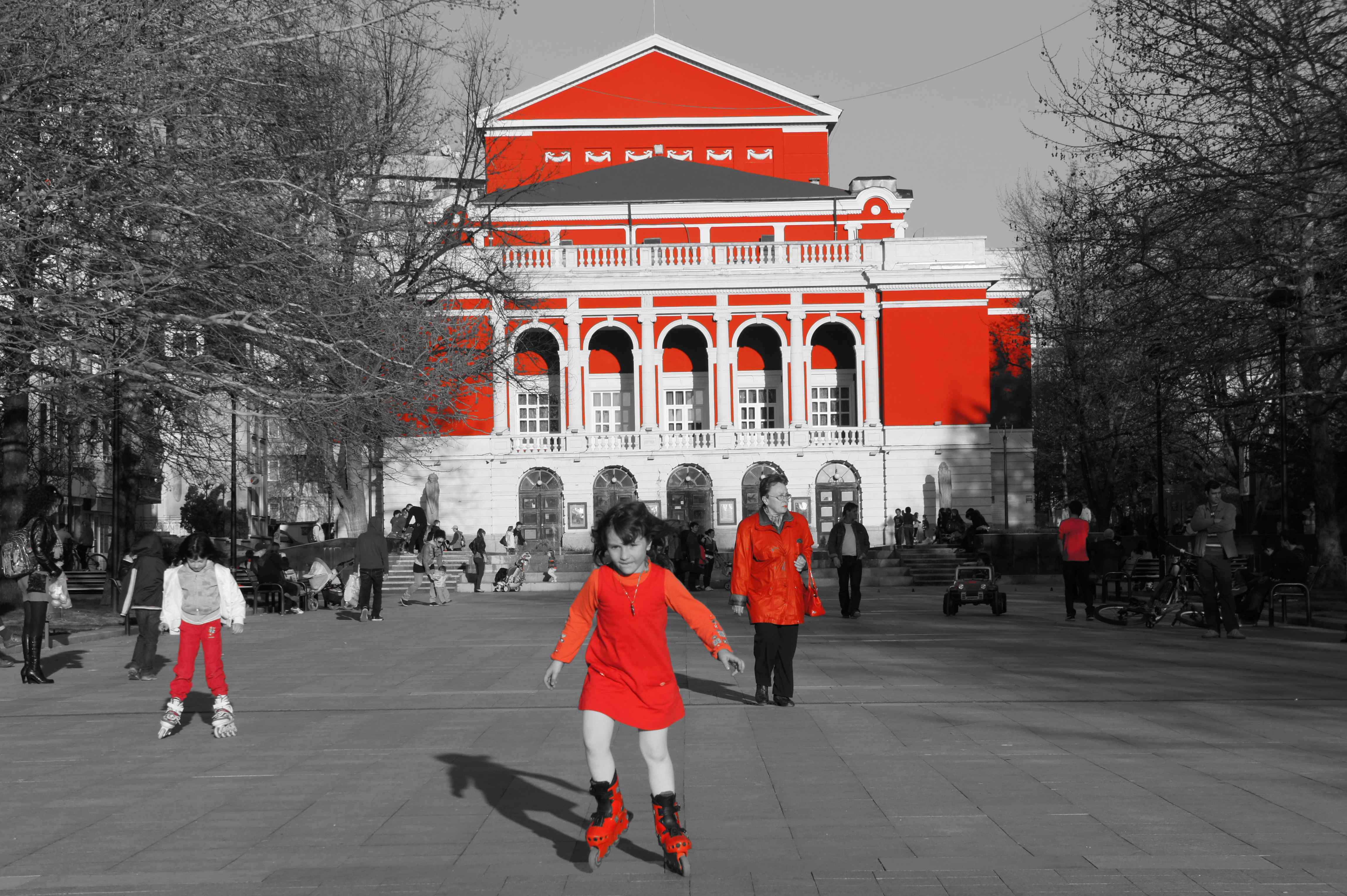 Colourful Russe - people in red in front of the red opera house