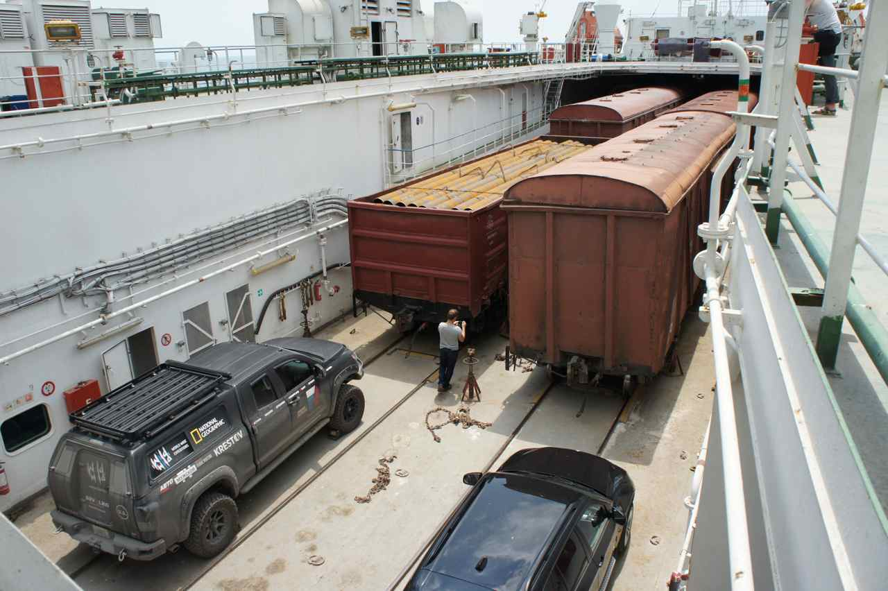 The deck in the aft of the ferry. Railway cars and the monster car from a National Geograpy photo team