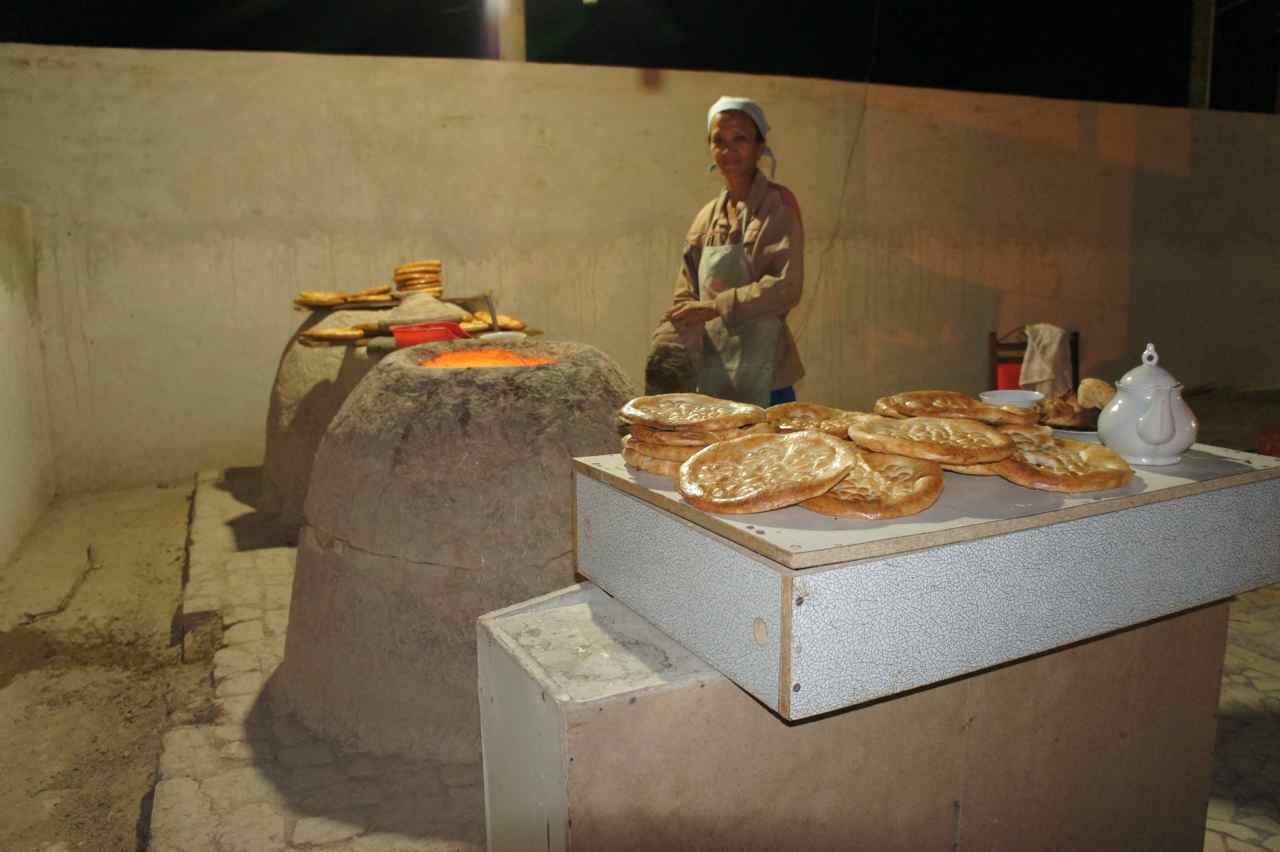 ด้านขวาของแคร่ที่นอนเรามีสาวคนนี้ยืนทำขนมปังที่เตาดินนั่น