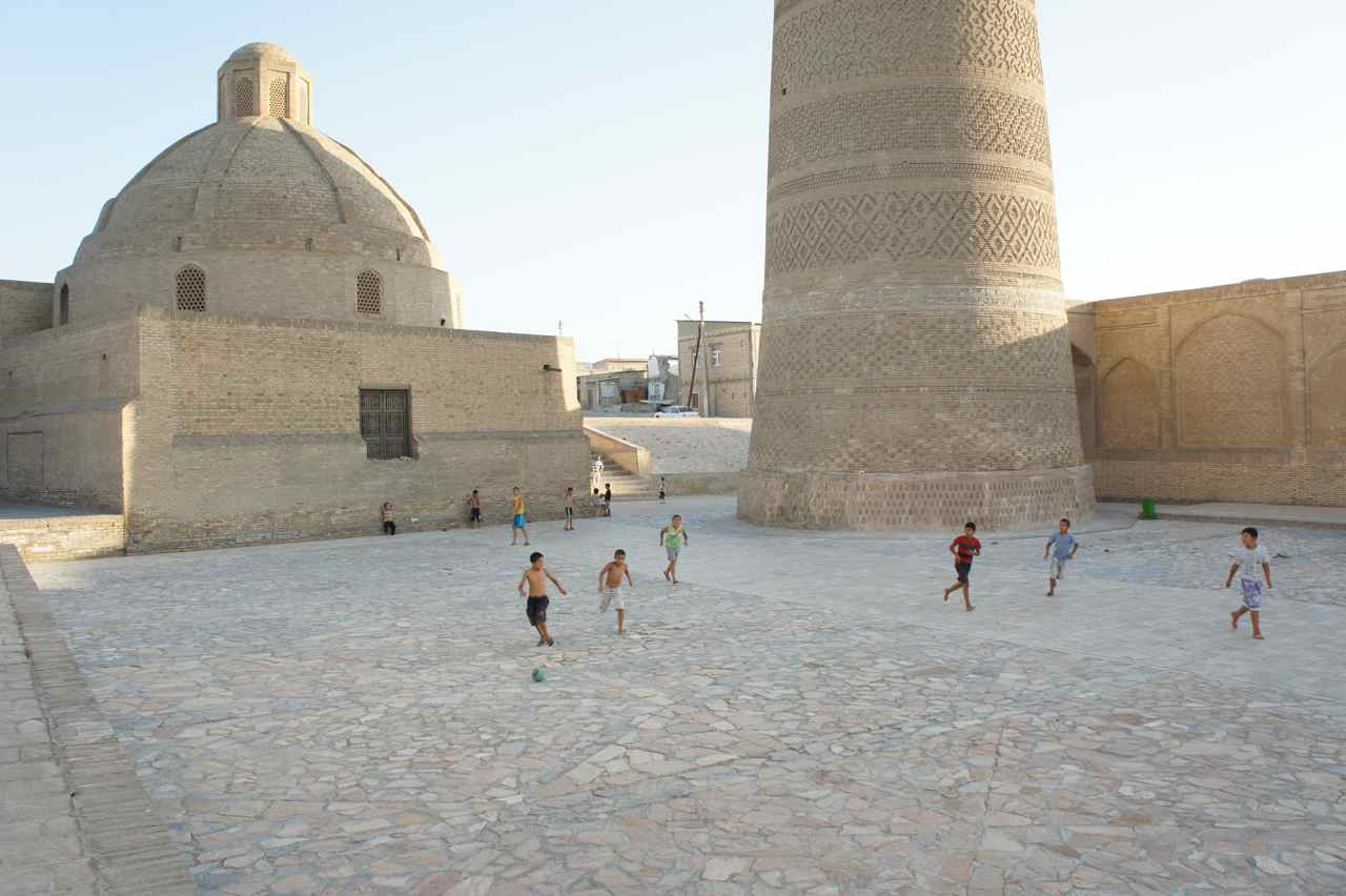 Young boys playing football in front of half a millenium old buildings