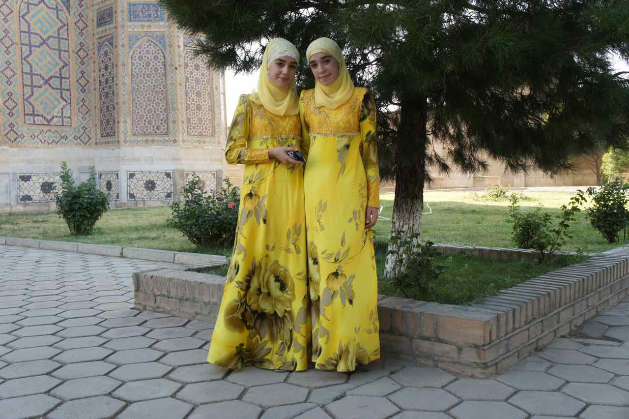 Two young girls in beautiful dresses visiting a mosque