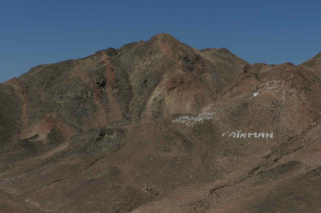 New type of grafitti - white stones on the red mountain side