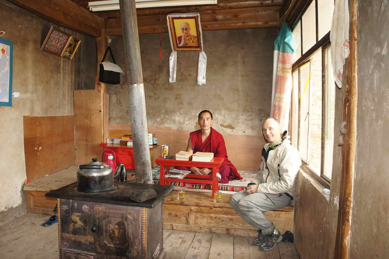 Having tea with the monk. Note the photo of Dalai Lama on the wall