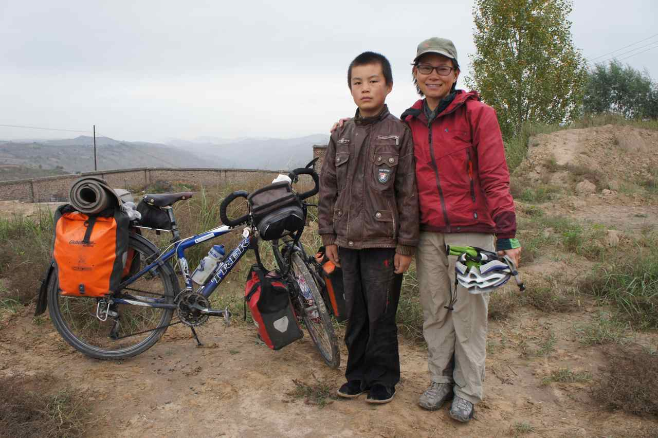 Wej and a curious local boy who came to watch us break our camp